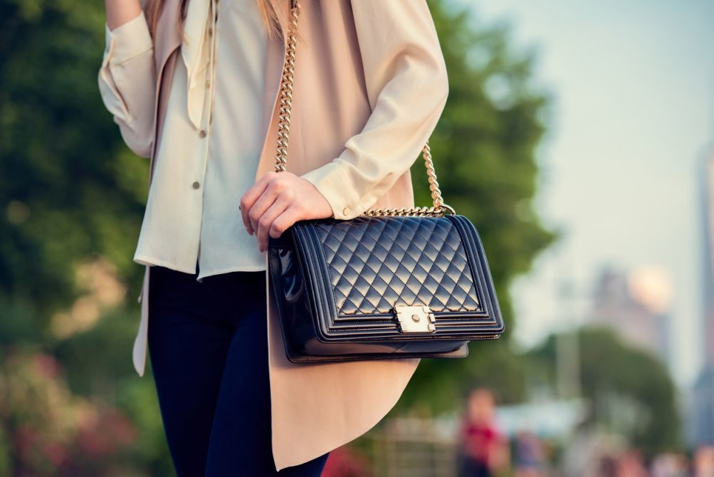 woman-carrying-elegant-purses-bag-at-city-park